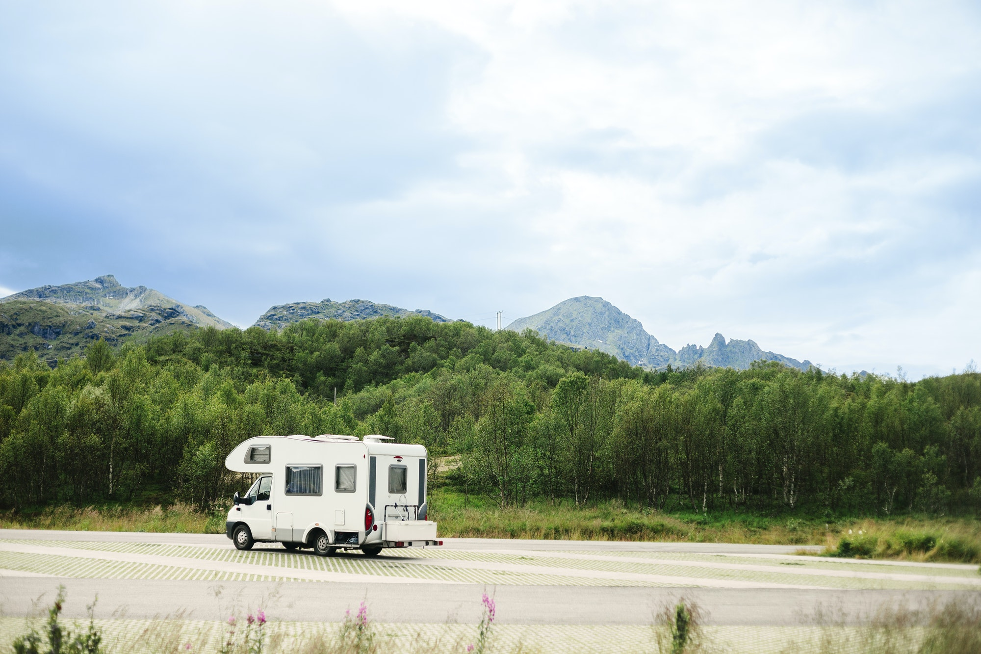 Caravan on mountain road against sky